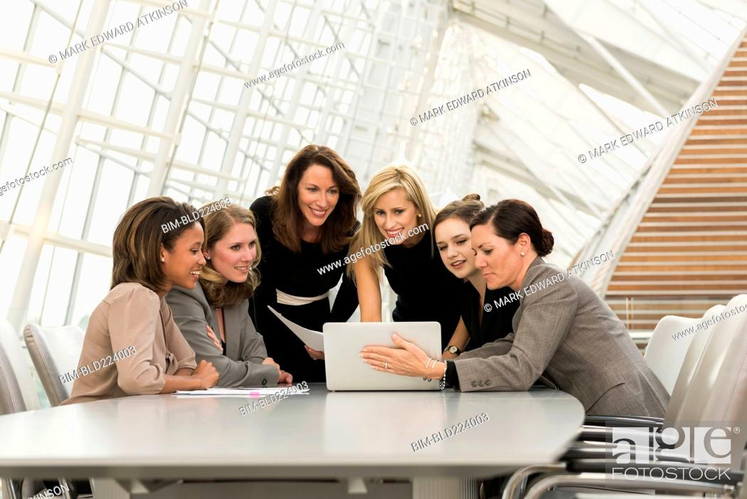 Stock Photo: Busy businesswomen using laptop in meeting.