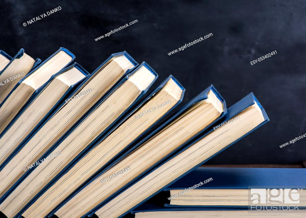 Imagen: uneven pile of books in the blue cover, black background, copy space.
