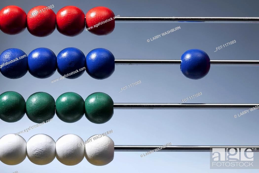 Stock Photo: Neat rows of colored beads on an abacus with a single blue bead to the side.