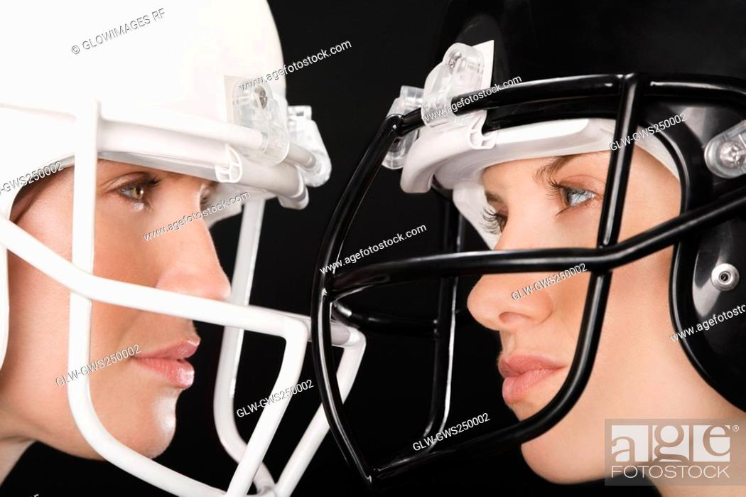 Stock Photo: Close-up of two businesswomen wearing football helmets and looking at each other.
