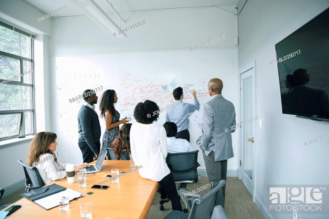 Stock Photo: Businessman writing on whiteboard in meeting.