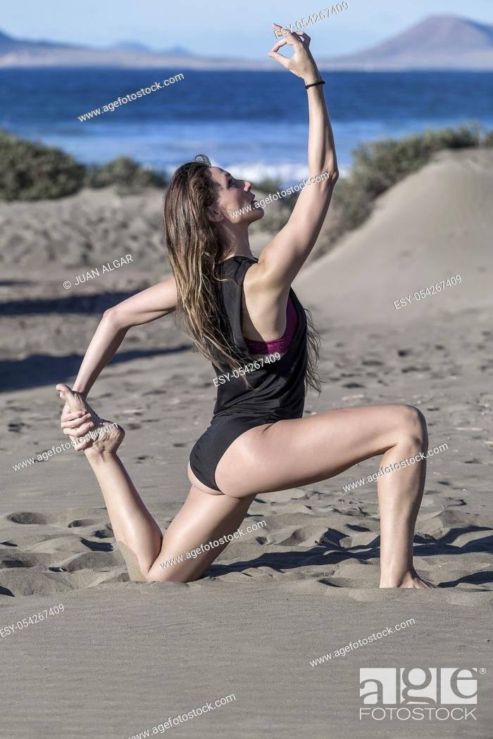 Stock Photo: Side view of slim brunette kneeling in yoga pose on seashore with bright sunlight.