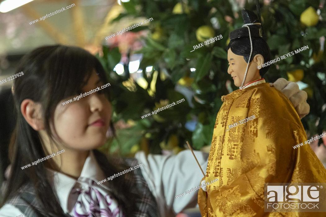 An employee looks at a Japanese 'hina' doll modeled after