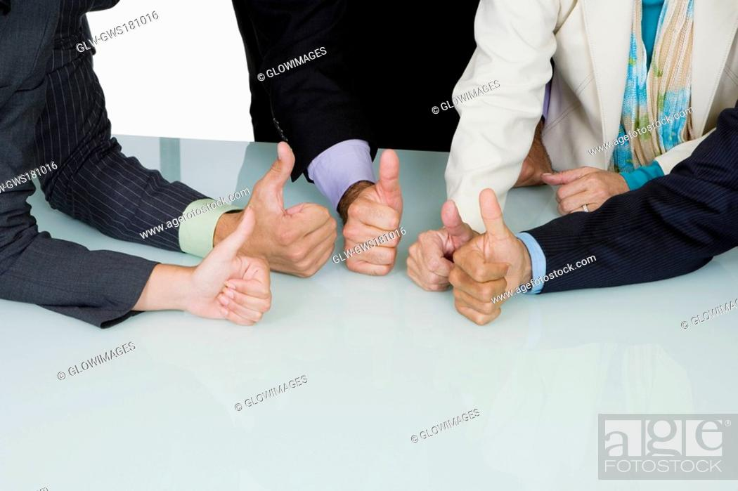Stock Photo: Five business executives showing thumbs up sign in a meeting.