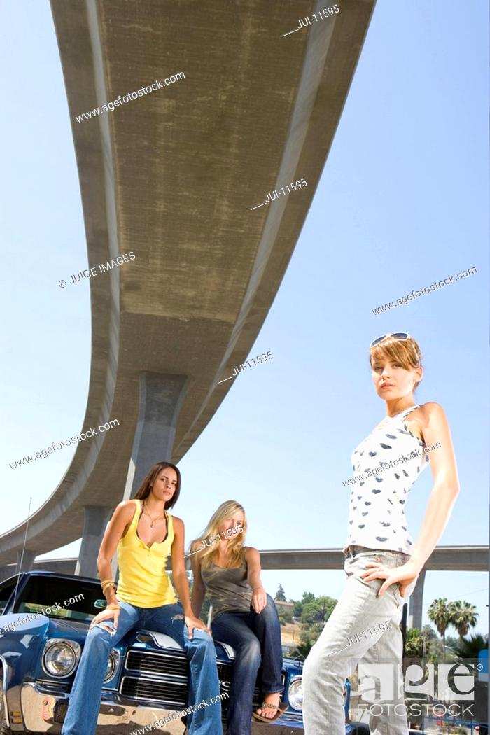 Stock Photo: Small group of young women by car beneath overpass, portrait, low angle view.