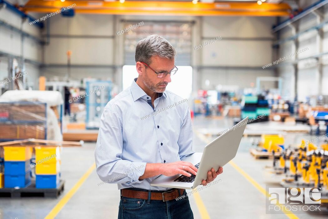 Stock Photo: Mature male engineer looking at laptop in engineering factory.