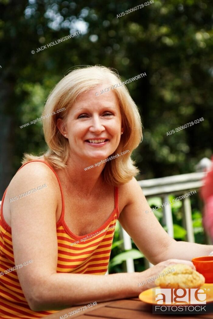 Stock Photo: Portrait of a mature woman sitting at the table and smiling.