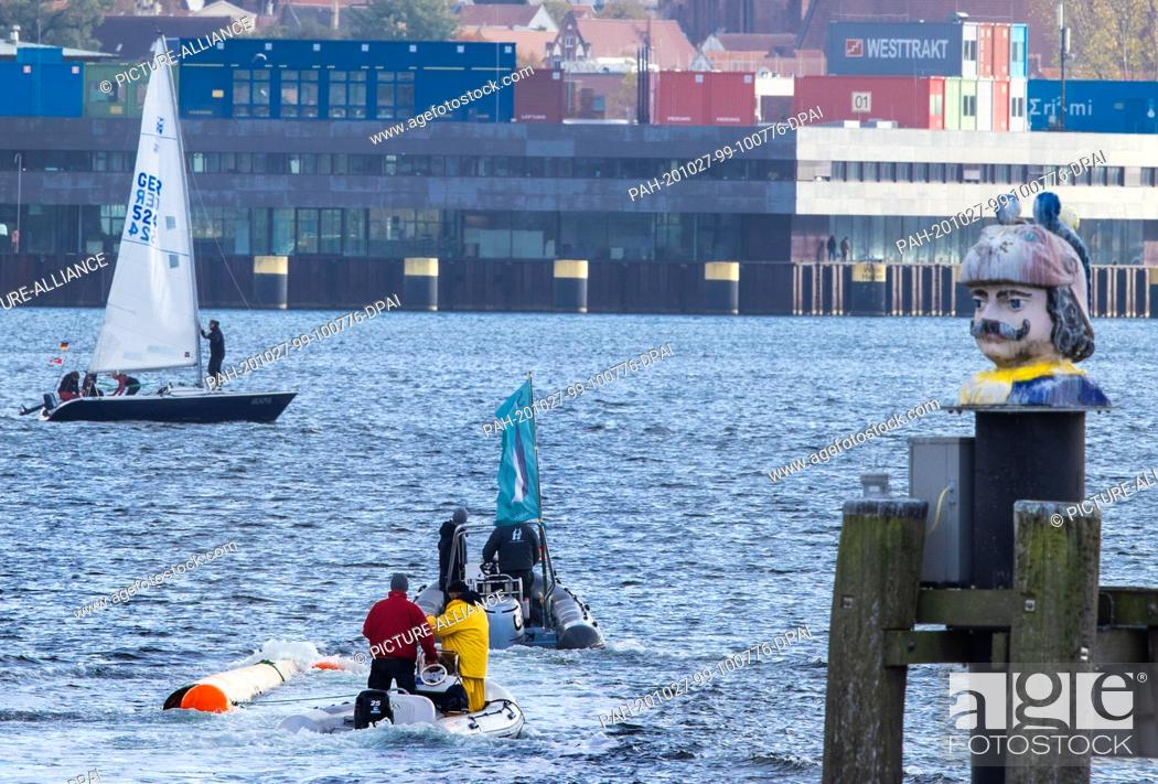 """Stock Photo: 27 October 2020, Mecklenburg-Western Pomerania, Wismar: The new mast for the sailing ship replica of the Poeler Kogge """"""""Wissemara"""""""" is towed into the harbour by."""