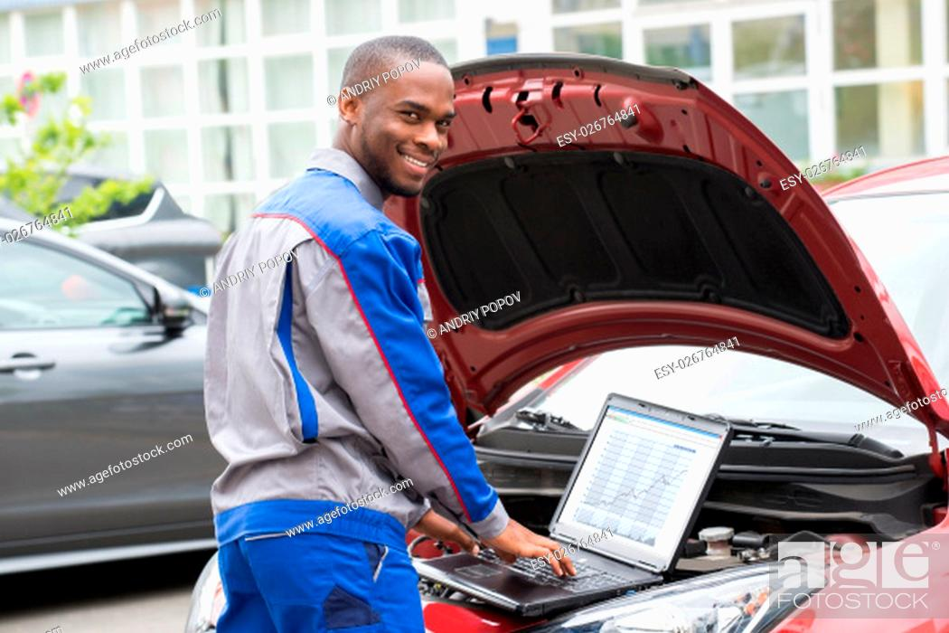 Stock Photo: Young Happy Mechanic Using Laptop In Front Of Open Car Engine.