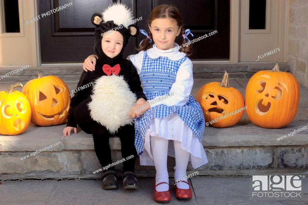 Stock Photo: Brother and Sister Dressed for Halloween Sitting on a Step, Toronto, Ontario.
