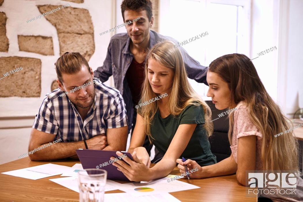 Stock Photo: Positive young professionals around a desk in a strategic planning meeting with a tablet pc and documents and notes strewn around the conference table.