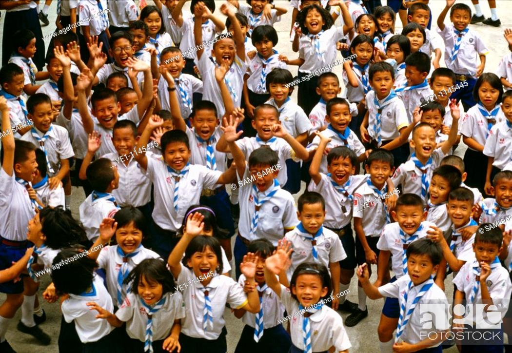 Stock Photo: Bangkok school children jumping and smiling at the camera, Thailand.