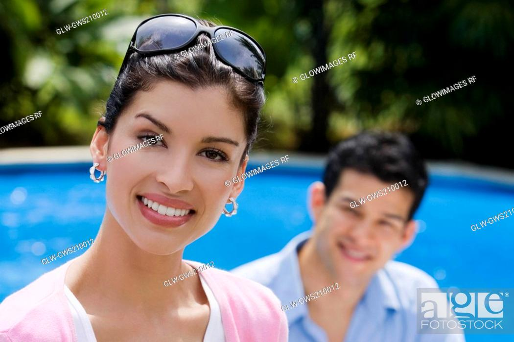 Stock Photo: Portrait of a young woman smiling with a young man in the background.