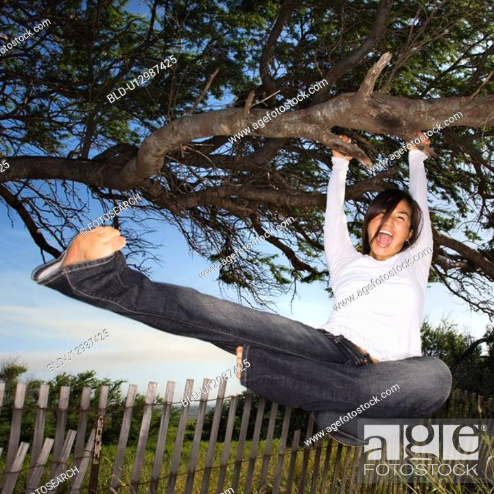 Stock Photo: Female holding on to tree and kicking air and screaming.