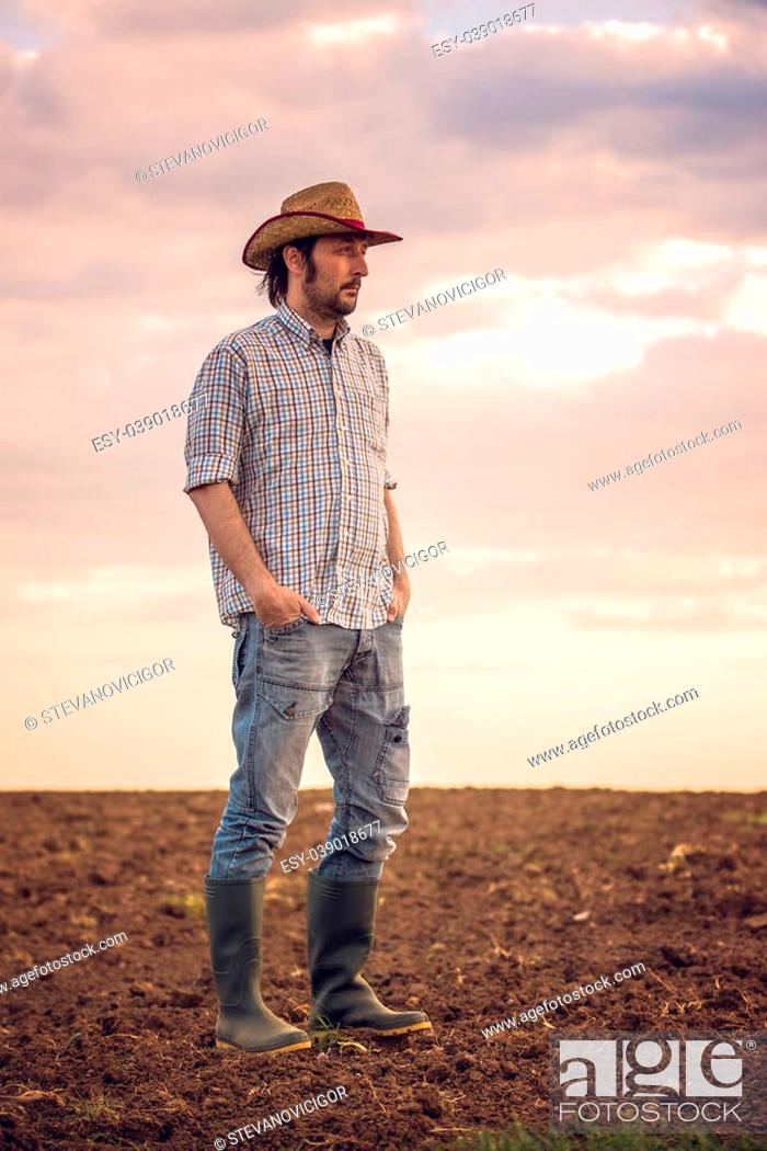 Stock Photo: Portrait of Adult Male Farmer Standing on Fertile Agricultural Farm Land Soil,Looking into Distance.