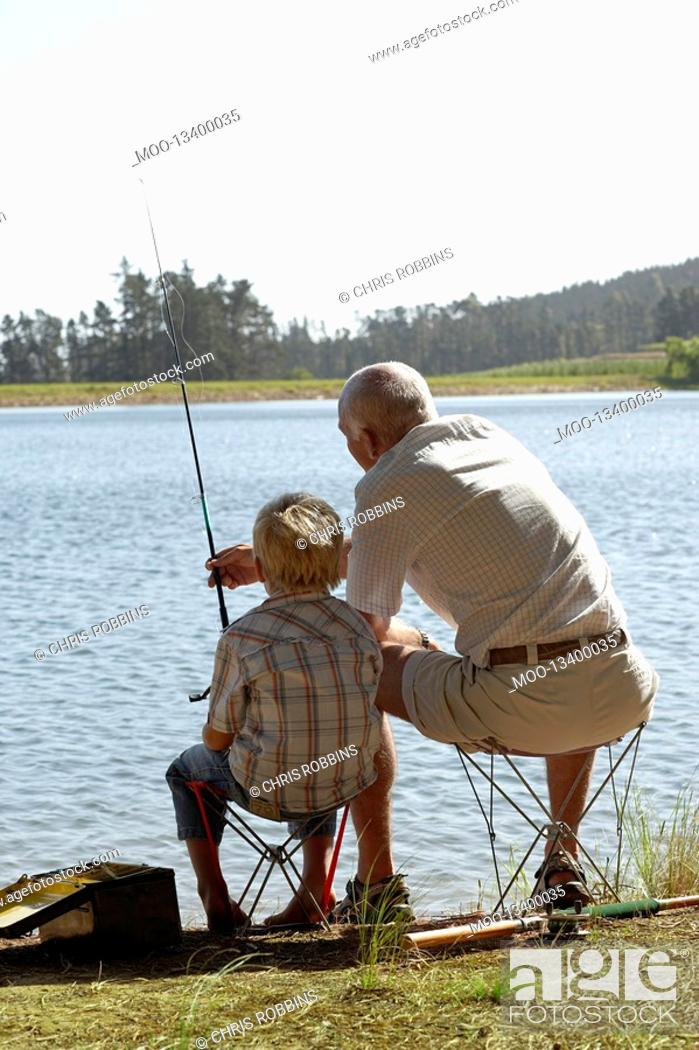 Stock Photo: Boy 7-9 fishing with grandfather back view.