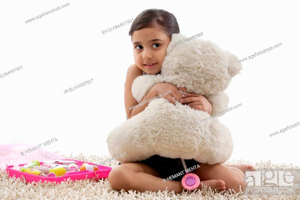 Stock Photo: Girl hugging her teddy bear.