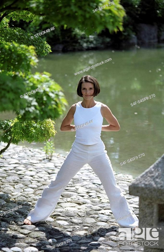 Stock Photo: Darkhaired Woman doing physical Exercise at the Shore of a Lake - Yoga - Harmony - Nature.