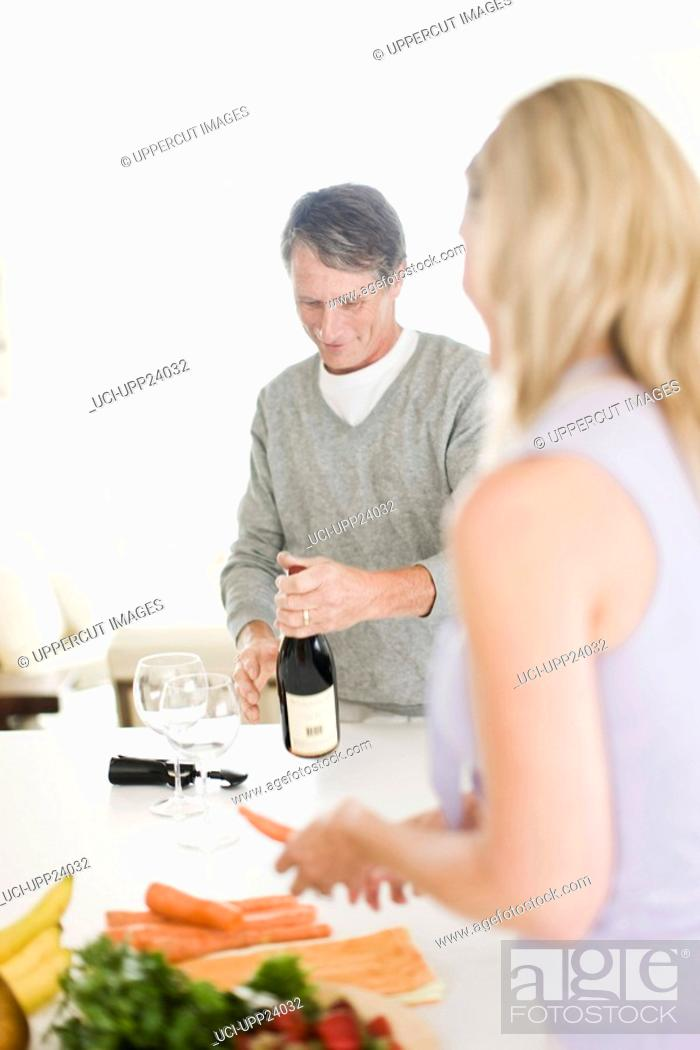 Stock Photo: Man opening bottle of wine and woman preparing food in kitchen.