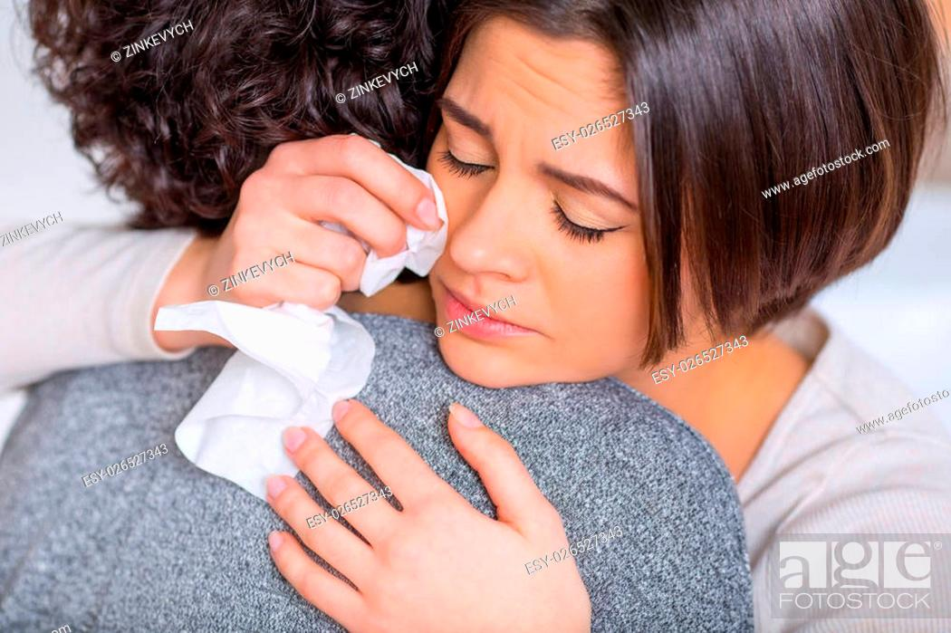 Stock Photo: Feeling sad. Young nice-looking woman is hugging her sister while weeping sadly.