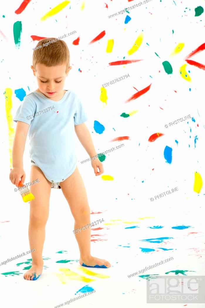 Photo de stock: Adorable 3 year old boy child creatively stains on the wall, floor with colourful paint. Mess of paint on wall, floor and everywhere.