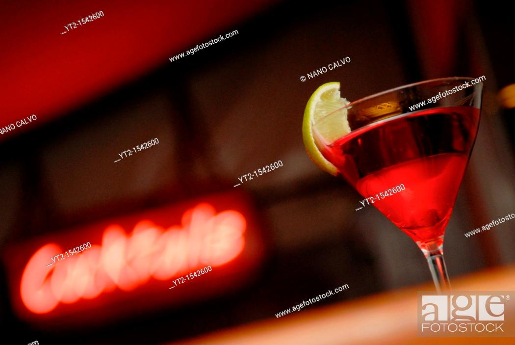 Stock Photo: Red cocktail and neon sign in a night bar.