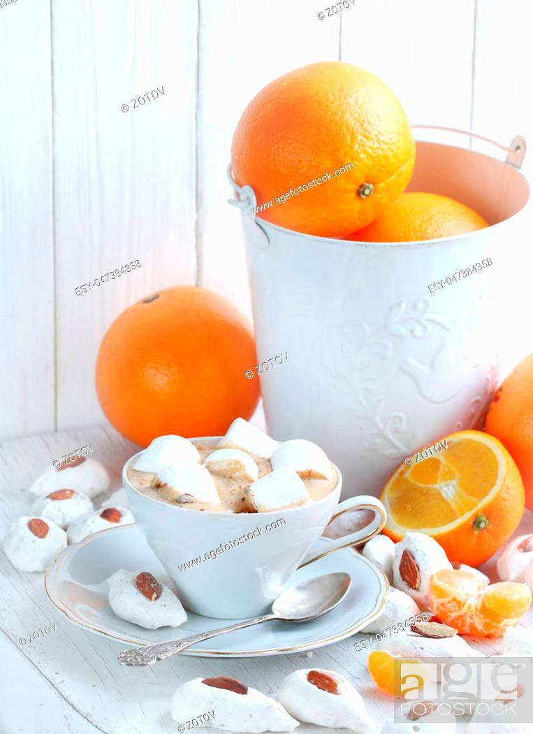 Stock Photo: Coffee cappuccino with meringue and oranges on a white background.