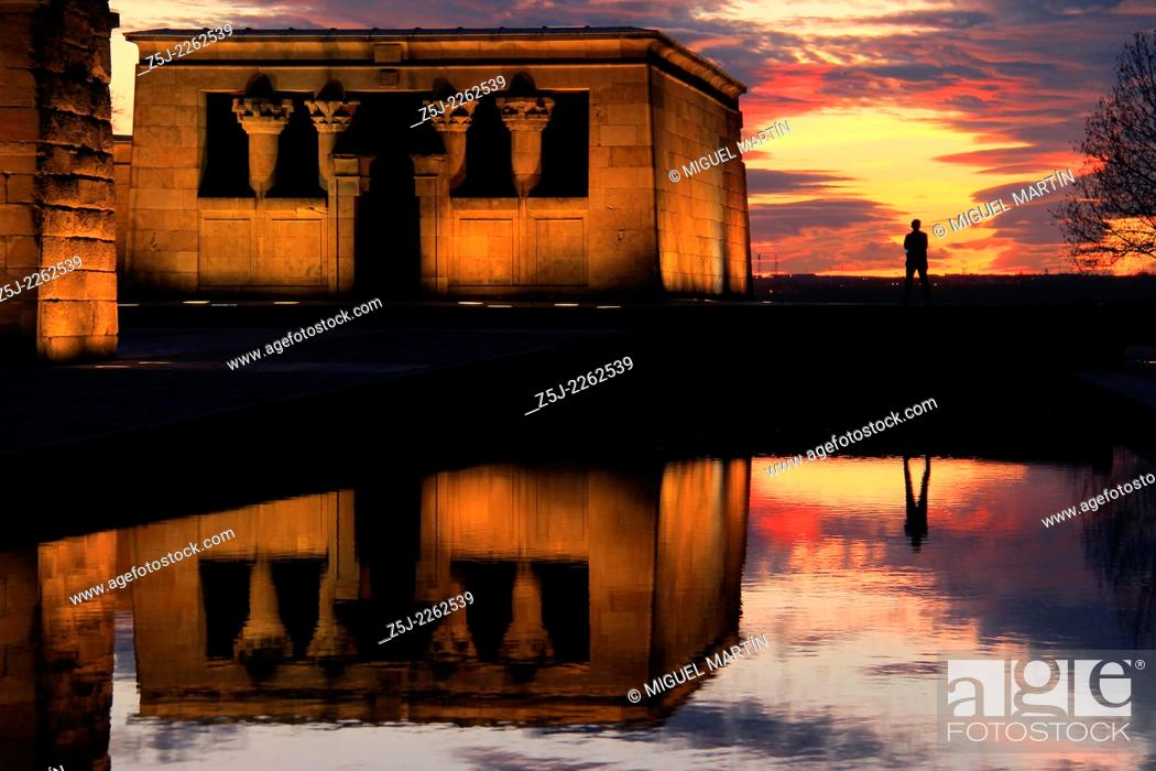 Stock Photo: A human silhouette framed by a spectacular sunset over Temple of Debod in Madrid, an Egyptian shrine donated by Egypt in 1968 in gratitude for Spanish help in.