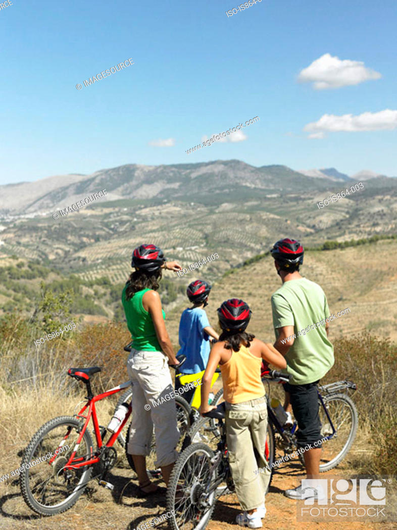 Stock Photo: Family with bicycles looking at view.