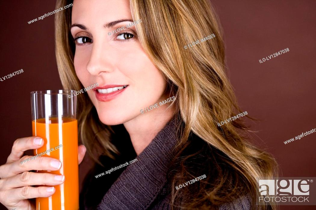Stock Photo: A mid adult woman holding a glass of fruit/carrot juice.