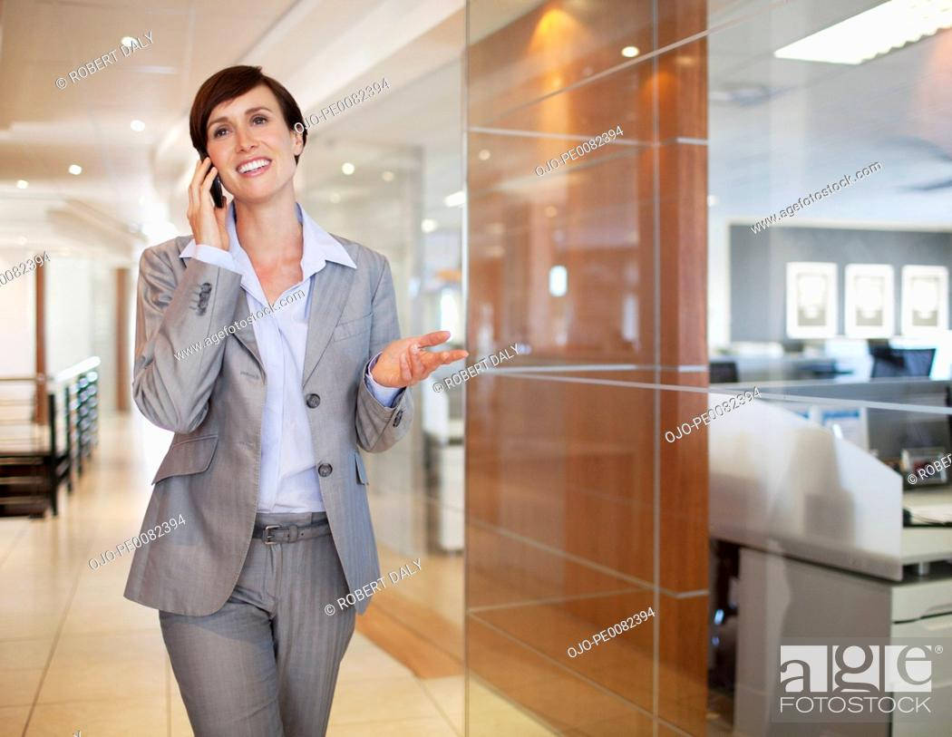 Stock Photo: Smiling businesswoman talking on cell phone in office corridor.