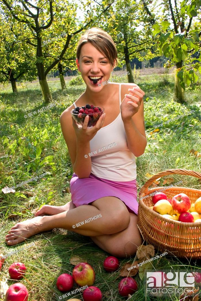 Stock Photo: Woman eating raspberries and blackberries in the garden.