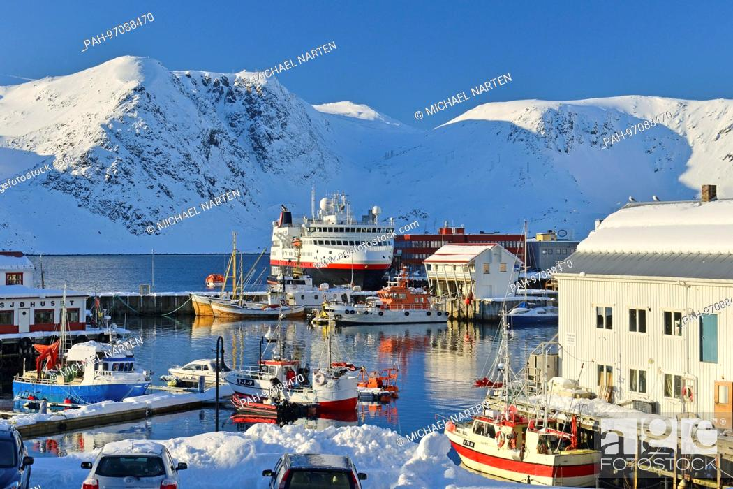 Stock Photo: Honningsvåg's harbour surrounded by snowcapped mountains full of boats with a Hurtigruten ship in the middle, 7 March 2017 | usage worldwide.