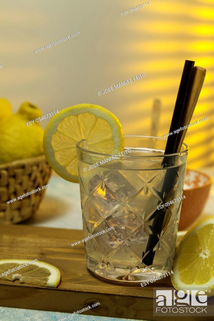 Stock Photo: lemonade glass with ice, spoon and straw on cutting board, cut lemons and basket with lemons on background with sunlight entering through rear window.