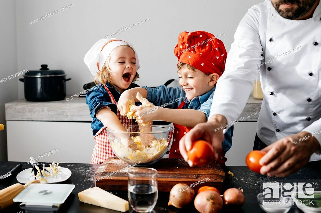 Photo de stock: Happy kids preparing dough with father in kitchen at home.