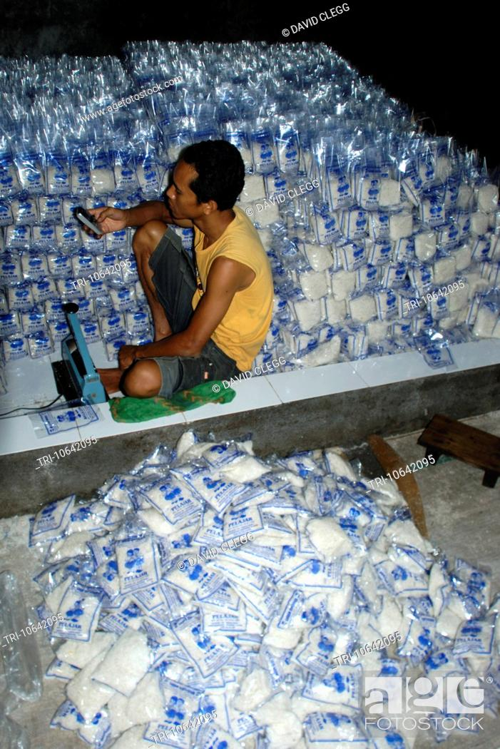 Stock Photo: Young man surrounded by clear plastic packets of salt checks his mobile phone in a small salt iodizing business Sakra Lombok Timur NTB Indonesia.