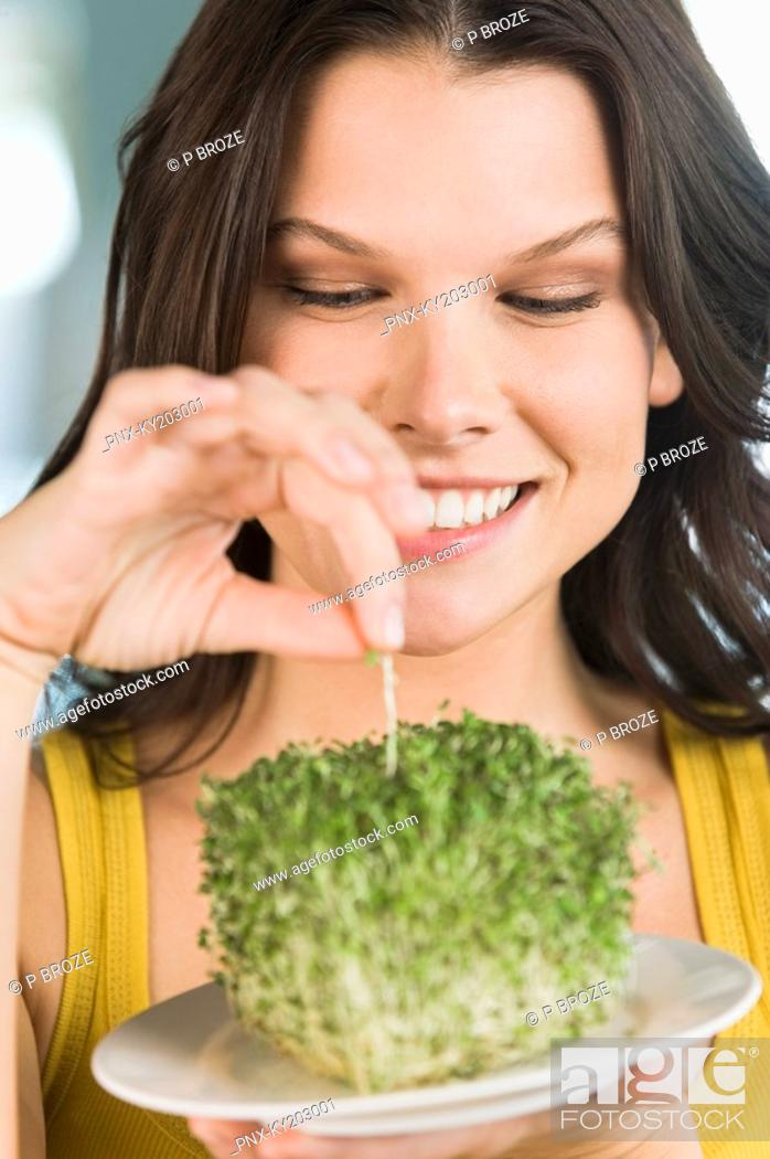 Stock Photo: Woman eating bean sprouts and smiling.