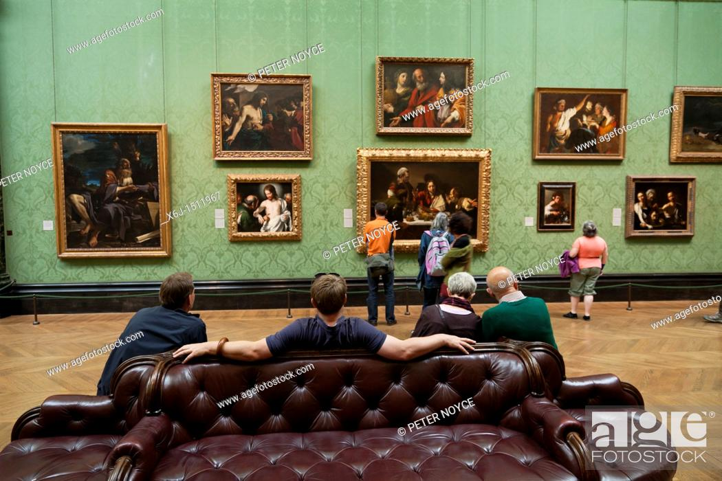 Stock Photo: viewing paintings including The Supper at Emmaus by Caravaggio in the Italy section of the National Gallery, london.