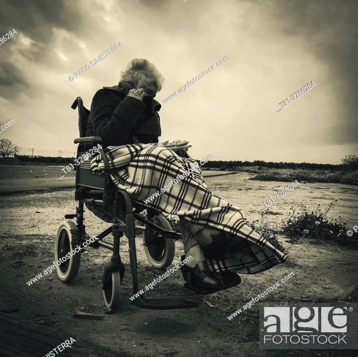 Stock Photo: Old woman in wheelchair shielding herself from the wind.