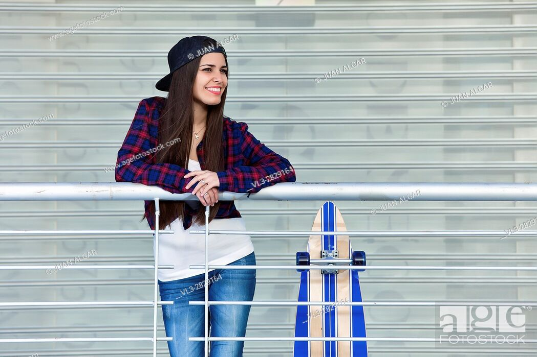Stock Photo: Shot of smiling female in cap standing near skate while posing for camera looking away.
