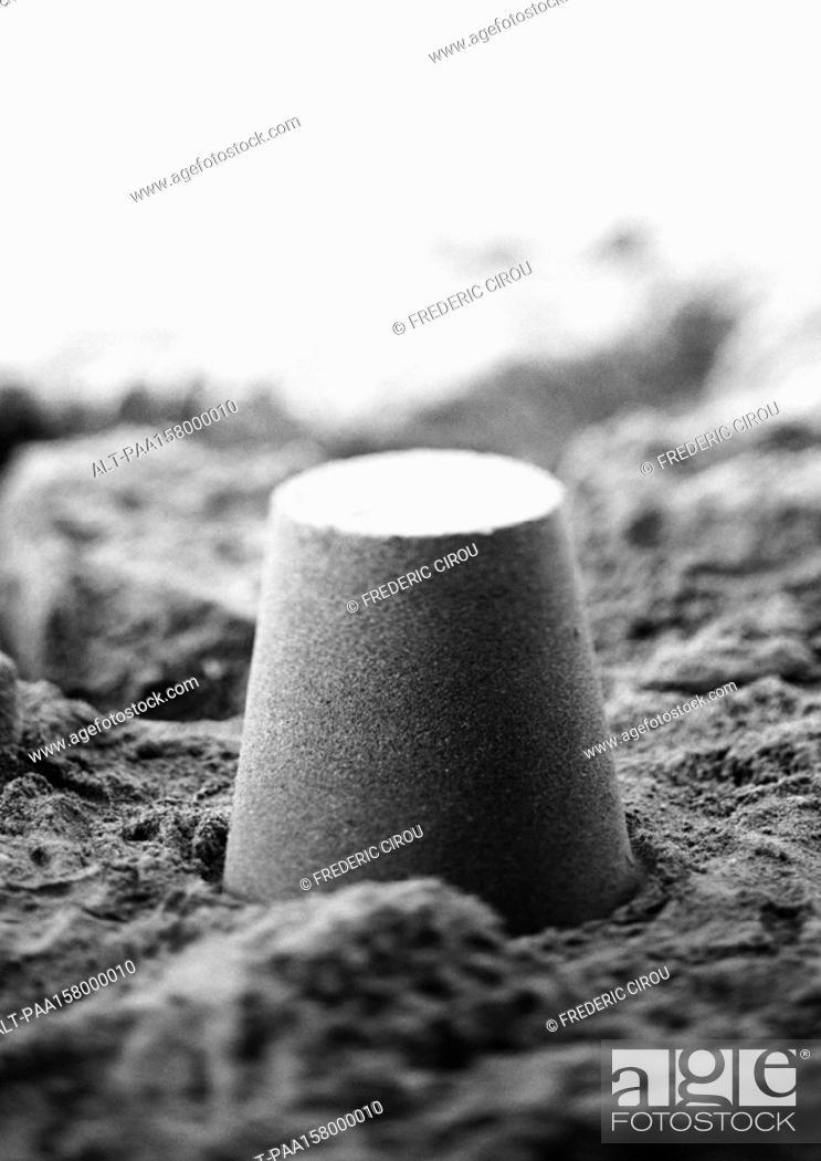 Stock Photo: Bucket-shaped pile of sand, b&w.