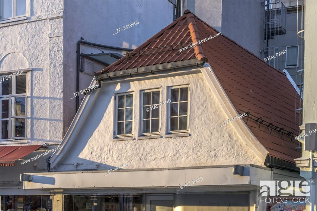 Stock Photo: picturesque roof of little building among taller ones, shot under bright low summer light at Bergen, Norway.