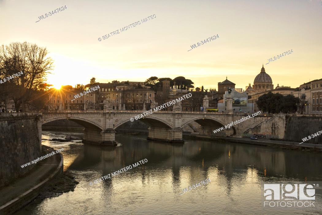 Stock Photo: Sunset on the bridge of Tiber river in Rome with the Vatican city in the background (Italy).