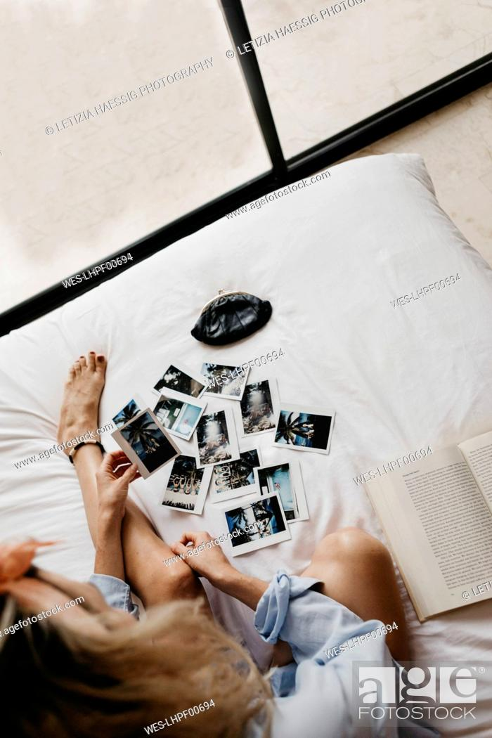 Stock Photo: Young woman in bed with book and polaroid pictures.