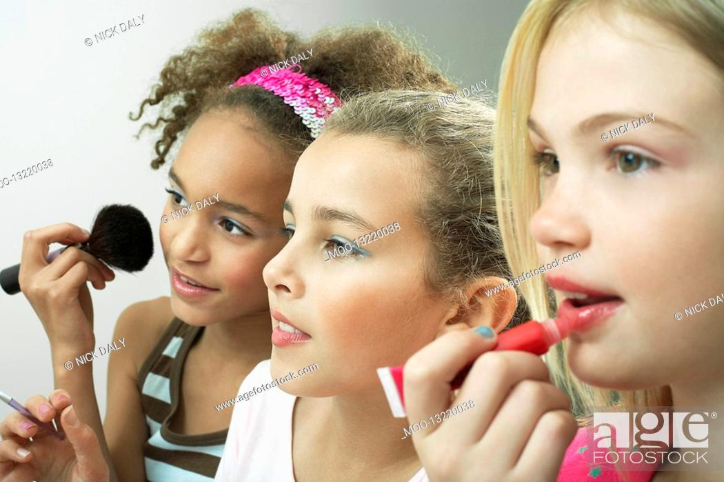 Stock Photo: Girls standing side by side putting on make-up and lip gloss.