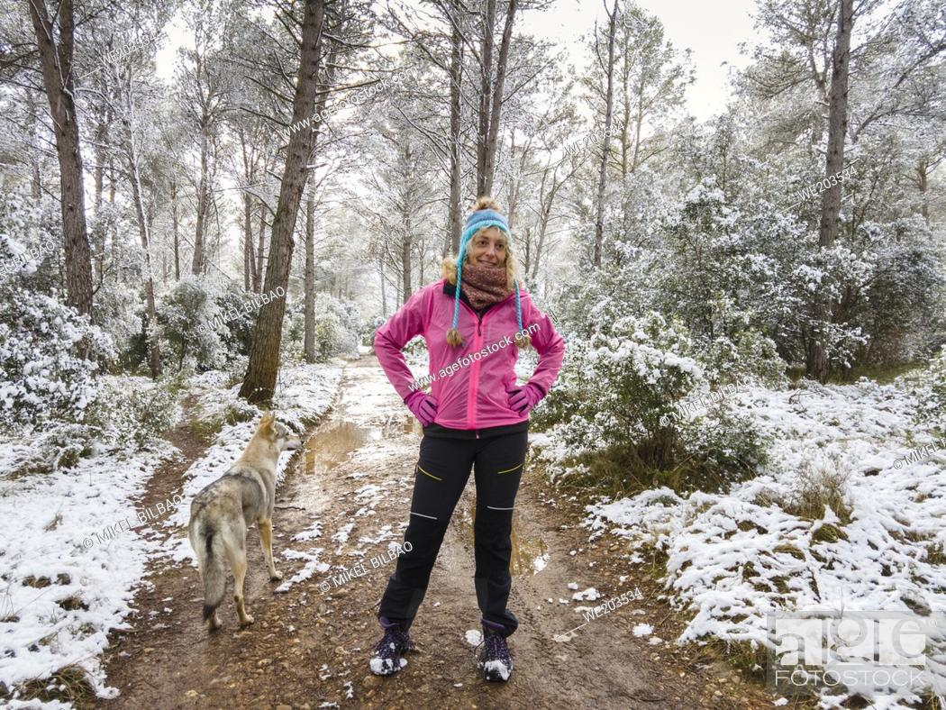 Imagen: Caucasian young woman with a wolf dog enjoying snow outdoor in a path in a forest area in winter time. Navarre, Spain, Europe.