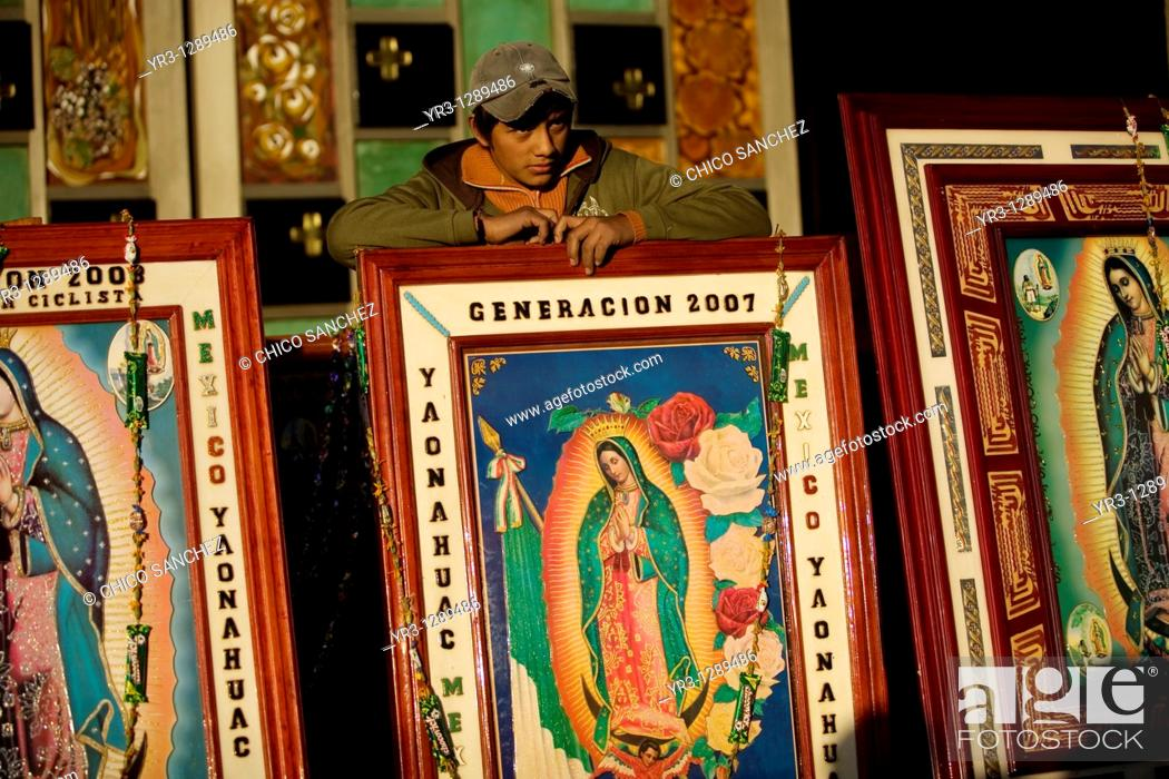 Stock Photo: A teenager stands behind images of Our Lady of Guadalupe in Mexico City, December 10, 2010  Hundreds of thousands of Mexican pilgrims converged on the Our Lady.