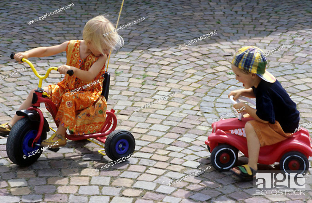 Stock Photo: Two children, little boy, little girl, 5-10 years old, playing in the garden, driving a three wheeler and a Bobbycar.