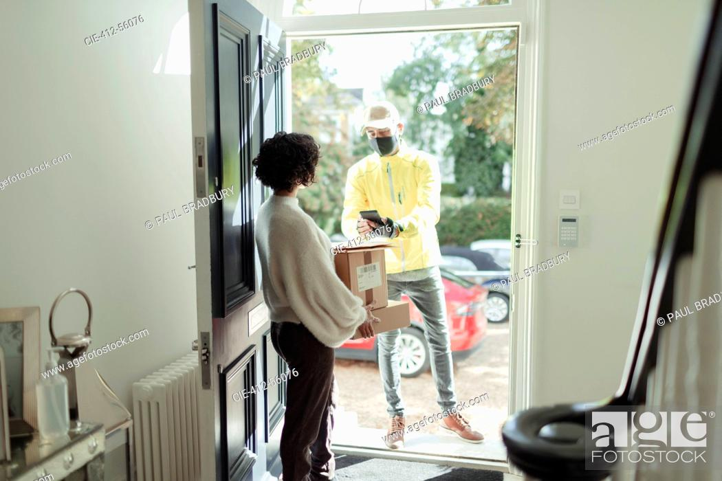 Stock Photo: Woman receiving package from delivery man in face mask at front door.