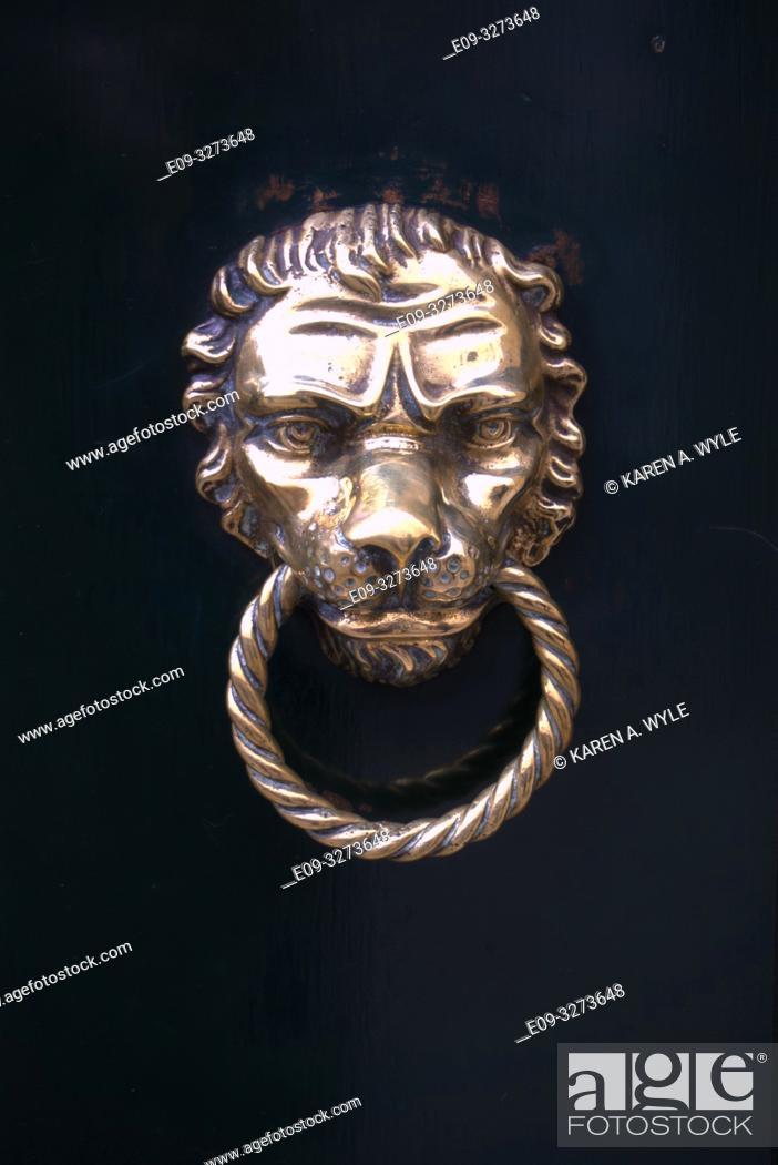 Stock Photo: brass lion-head door knocker on black door, Venice, Italy.